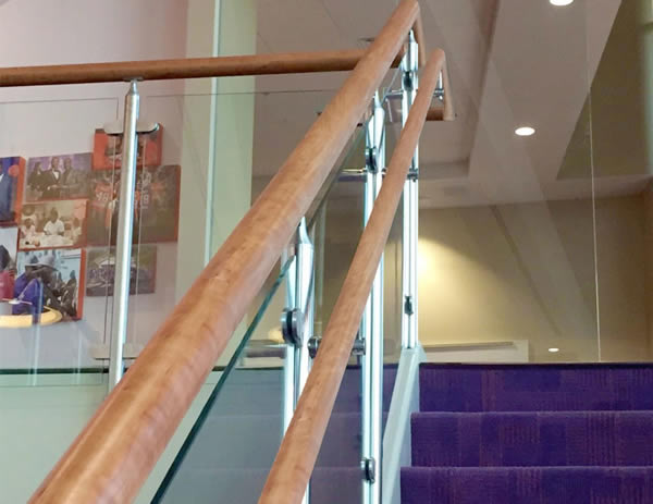 Custom wood top cap and handrails were utilized on both the cable and glass railing systems on stair and balcony overlooks throughout the facility