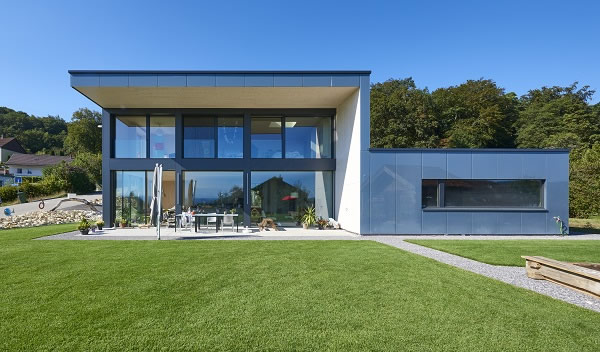 On the south-facing aspect, the structure opens up to the outside with a large glass façade. Subtle reflections mirror the surroundings.