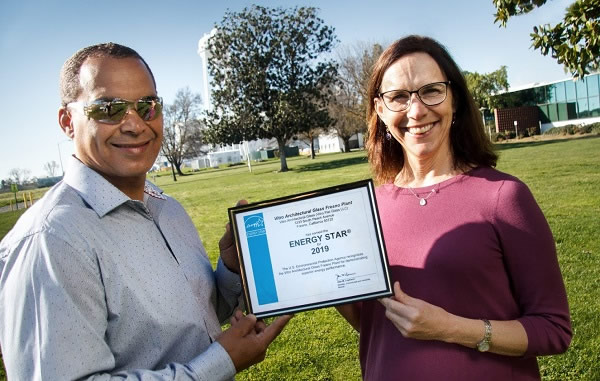 Vitro Architectural Glass employees Glen Collins, Fresno plant supervisor (left), and Wendy Garcia, environmental manager, receive an ENERGY STAR-labeled plant certificate for the company's Fresno, California plant.