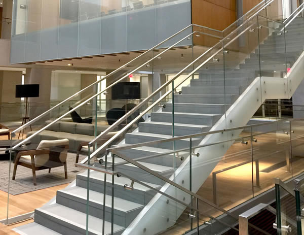 Glass infill is brought down to be flush with soffit. Facility features over 2,400 ft. of custom stainless steel flat bar handrail – 825 ft. of that is wall mounted.