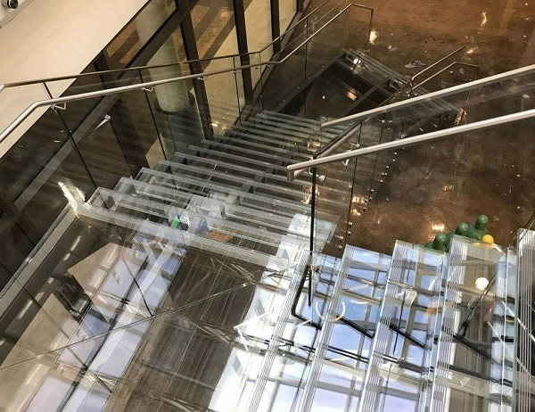 Glass treads and risers, combined with the Trex Commercial Products' Point Series railing system, give this staircase a seamless, barely there appearance.