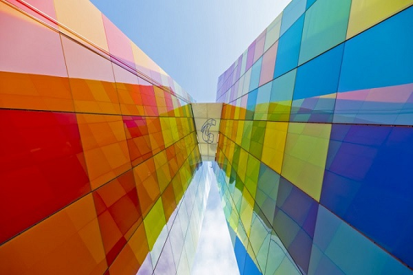 Arranged in a harlequin pattern, the glazed panels − in shades of red, yellow, green, blue and white − cover the entirety of the structure in a multi-colored façade. Image © Tecnoglass