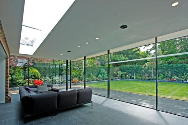 KELLER minimal windows® as floor to ceiling sliding glass walls to rear extension