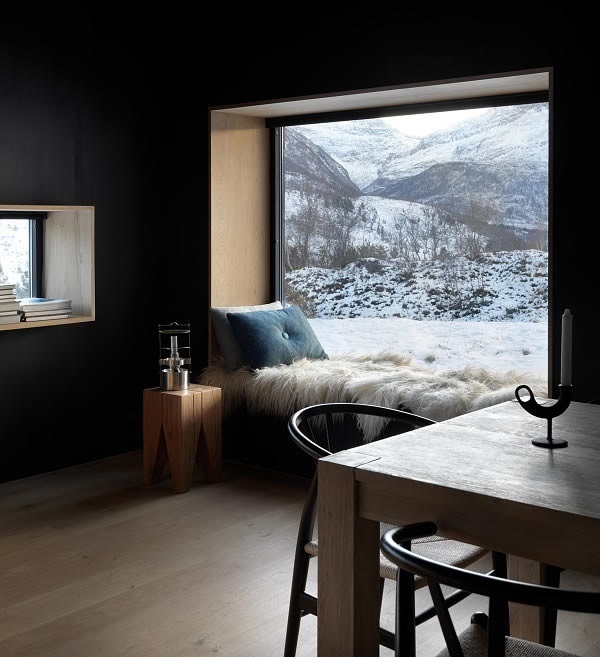 Photo Credits: Invit Arkitekter, Ålesund // Photographer: Johan Holmquist Cozy corner with a view: without energy losses, the seasonal dynamics of nature become a decorative picture (façade system Schüco FW 50+.SI).