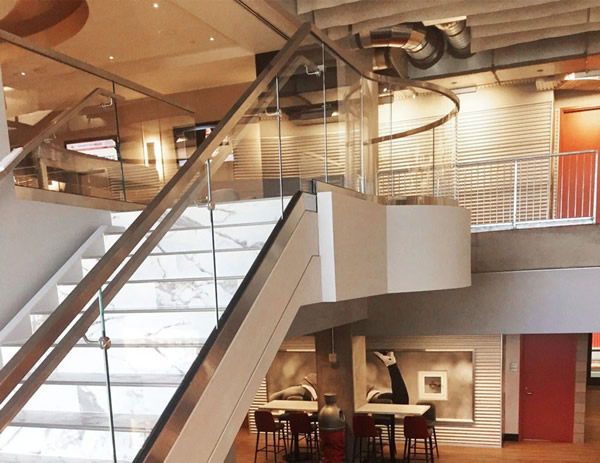 A custom, square stainless steel handrail was attached to the glass railing using through-glass standoffs, offering strong support with a minimalist look.