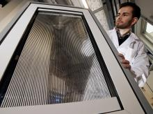 A prototype of the innovative smart windows for controlled shading and solar thermal energy harvesting is presented by PhD student Benjamin Heiz from the research group of Lothar Wondraczek. | Photo: Jan-Peter Kasper/FSU