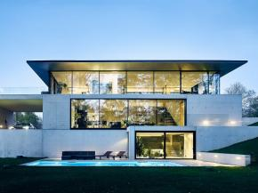 "What architects OUTOFBOX describe as ""ascetic design"" presents itself as an impressive glass and concrete building, modestly embedded within the terraced landscape."