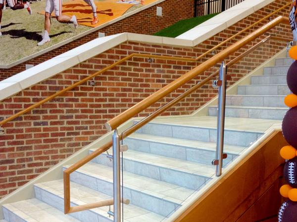 Top mounted Monaco railing with wood top cap and handrail utilized the D-shaped clamp to secture glass infill