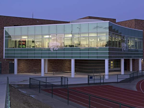 Novi High School's new fitness center features curved Tubelite curtainwall with stadium views, welcoming interior