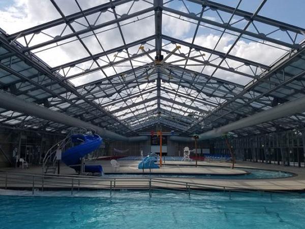 Unique indoor outdoor pool design for batesville community for Pool design center