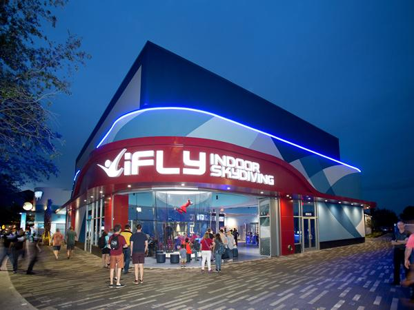 Spectators gathering around a flying person in iFly's flying tunnel.
